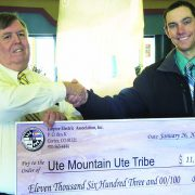 Bob Brooker, Ute Mountain Travel Center and Casino General Manager, receives a rebate check from Dellinger.